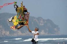 A man holds a two dimensional kite at the 2016 National Kite Festival on Parangkusumo Beach in Bantul, Yogyakarta. JP/ Aditya Sagita