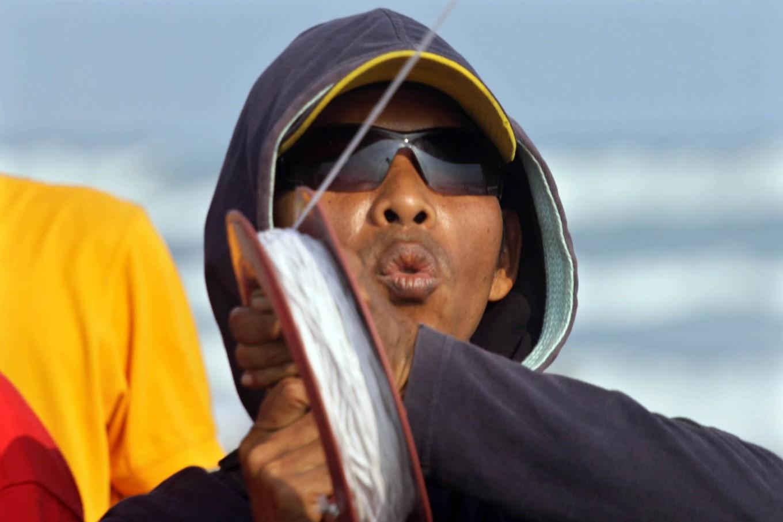 A participant of 2016 National Kite Festival controls his kite. JP/ Aditya Sagita