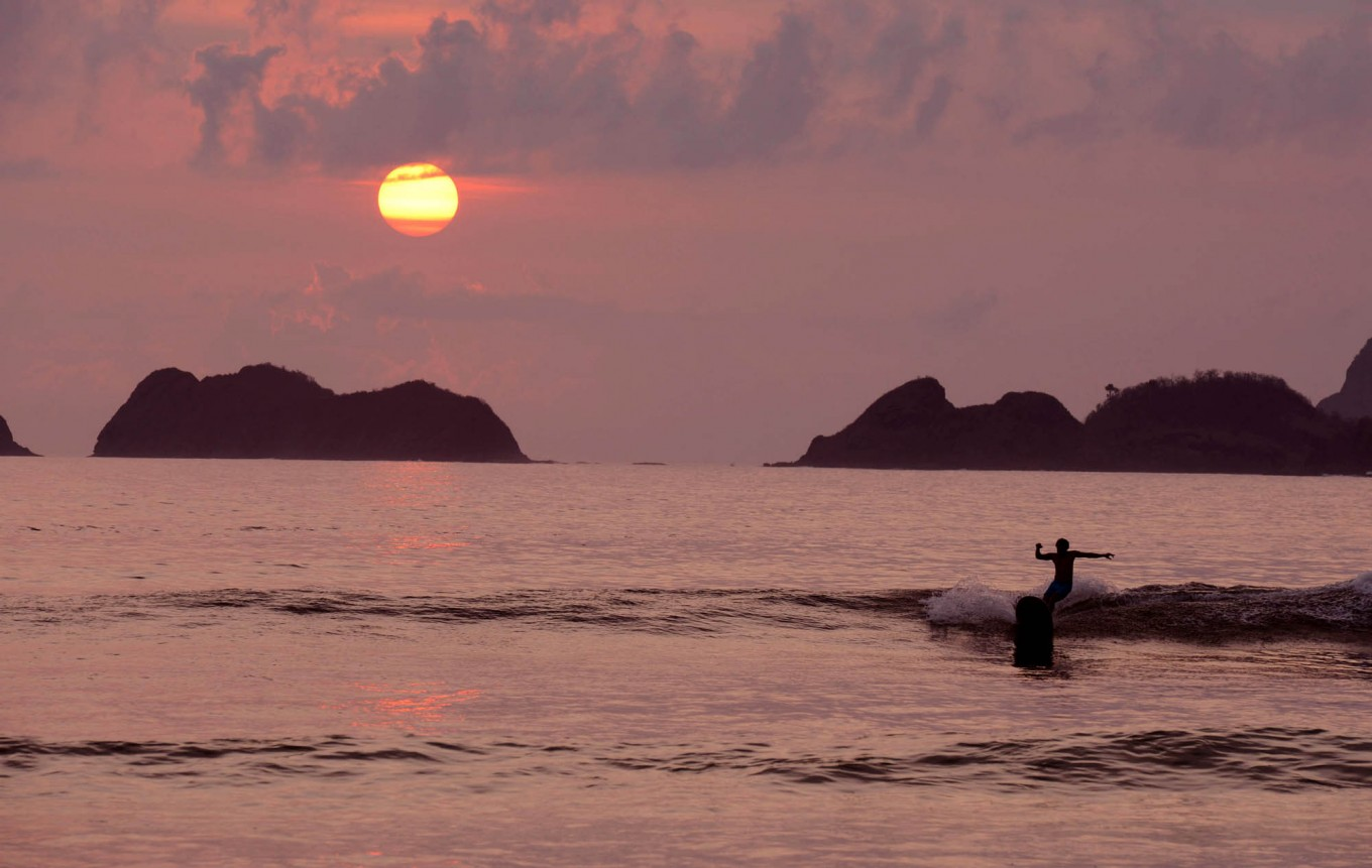 A surfer catches a ride near the island, which is a popular spot for surfing. JP/Tarko Sudiarno