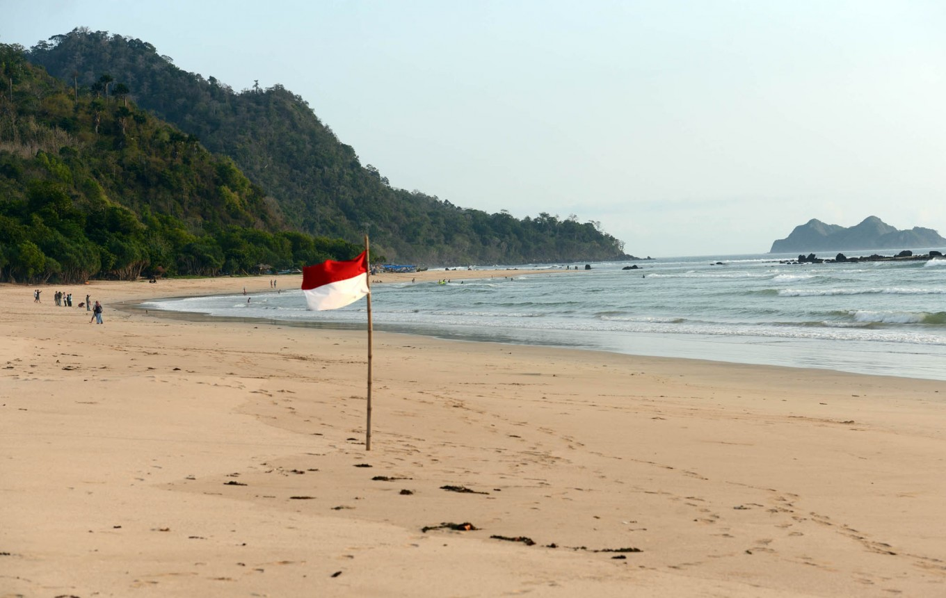A red-and-white flag blows in the wind on a beach near the island. JP/Tarko Sudiarno