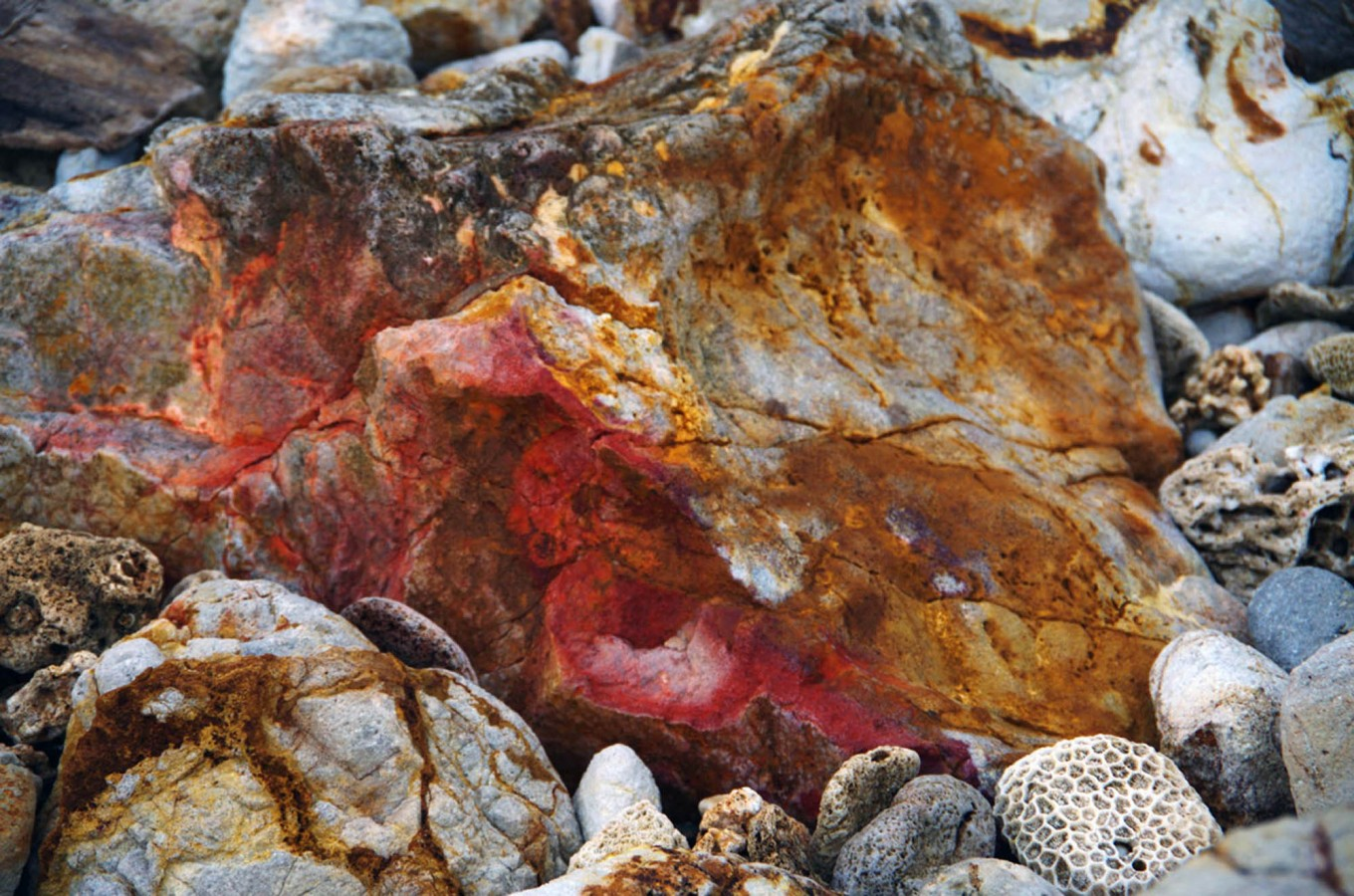 A red section of rock is seen on a beach on Pulau Merah. JP/Tarko Sudiarno