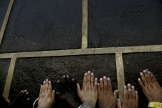 In this Wednesday, Sept. 7, 2016 file photo, Muslim pilgrims reach the Kaaba, Islam's holiest shrine, to touch it for blessing at the Grand Mosque in the Muslim holy city of Mecca, Saudi Arabia. Muslim pilgrims have begun arriving at the holiest sites in Islam ahead of the annual hajj pilgrimage in Saudi Arabia, with some weeping with their hands outstretched for a fleeting touch of the Kaaba. The cube-shaped shrine, at the center of Mecca's Grand Mosque, is the site the world's 1.6 billion Muslims pray toward five times a day. AP Photo/Nariman El-Mofty