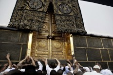 In this Wednesday, Sept. 7, 2016 file photo, Muslim pilgrims touch the golden door of the Kaaba, Islam's holiest shrine, at the Grand Mosque in the Muslim holy city of Mecca, Saudi Arabia. Muslim pilgrims have begun arriving at the holiest sites in Islam ahead of the annual hajj pilgrimage in Saudi Arabia, with some weeping with their hands outstretched for a fleeting touch of the Kaaba. The cube-shaped shrine, at the center of Mecca's Grand Mosque, is the site the world's 1.6 billion Muslims pray toward five times a day. AP Photo/Nariman El-Mofty
