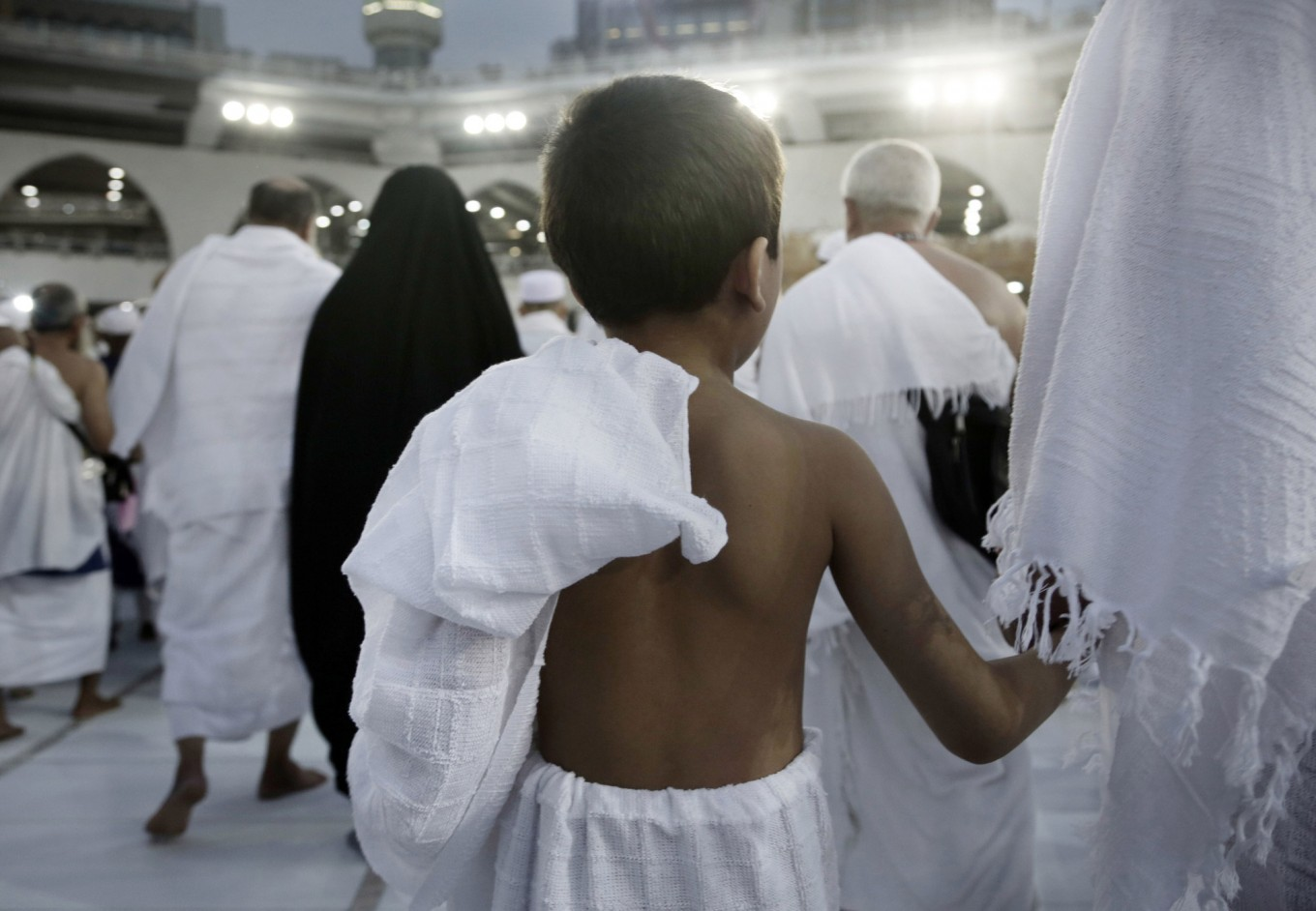 A child holds on to his father as he circles the Kaaba, Islam's holiest shrine, at the Grand Mosque in the Muslim holy city of Mecca, Saudi Arabia, Thursday, Sept. 8, 2016. Muslim pilgrims have begun arriving at the holiest sites in Islam ahead of the annual hajj pilgrimage in Saudi Arabia, with some weeping with their hands outstretched for a fleeting touch of the Kaaba. The cube-shaped shrine, at the center of Mecca's Grand Mosque, is the site the world's 1.6 billion Muslims pray toward five times a day. AP Photo/Nariman El-Mofty
