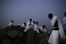 An African man reaches the top of Noor Mountain, where Prophet Muhammad received his first revelation from God to preach Islam, on the outskirts of Mecca, Saudi Arabia, Friday, Sept. 9, 2016. Muslim pilgrims have begun arriving at the holiest sites in Islam ahead of the annual hajj pilgrimage in Saudi Arabia. The Mecca Royal Clock Tower Hotel is seen at center. AP Photo/Nariman El-Mofty