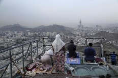 Chechens pray atop of Noor Mountain, where Prophet Muhammad received his first revelation from God to preach Islam, as Egyptians at right watch the view, on the outskirts of Mecca, Saudi Arabia, Friday, Sept. 9, 2016. Muslim pilgrims have begun arriving at the holiest sites in Islam ahead of the annual hajj pilgrimage in Saudi Arabia. The Mecca Royal Clock Tower Hotel is seen at center. AP Photo/Nariman El-Mofty