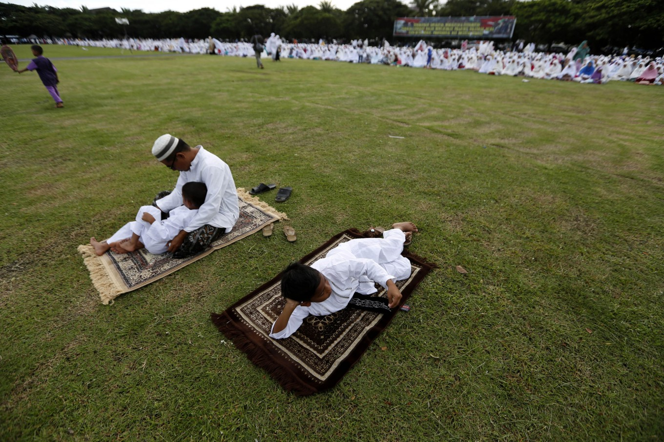 Two boys and a father lie on their prayer mats after conducting Idul Adha prayers in Banda Aceh on Sept. 12. JP/ Hotli Simanjuntak