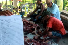 Several men slice meat to be distributed for poor people in Poowo Village of Bone Bolango regency, Gorontalo, on Sept. 12. Besides mosques and open fields, the slaughtering process was also conducted in several residential houses for this year's Idul Adha. JP/Syamsul Huda M. Suhari