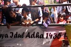 Children observe the animal slaughtering process during Idul Adha celebrations at Jogokariyan Mosque in Yogyakarta on Sept. 12. JP/Aditya Sagita