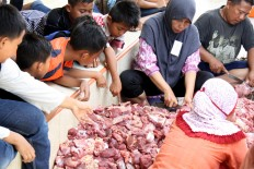 Children look on as piles of meat are sliced into pieces by the Idul Adha qurban committee. The meat was distributed to local people for the Idul Adha celebration at Al Ikhwan Mosque in Medan, North Sumatra, on Sept. 12. JP/Apriadi Gunawan
