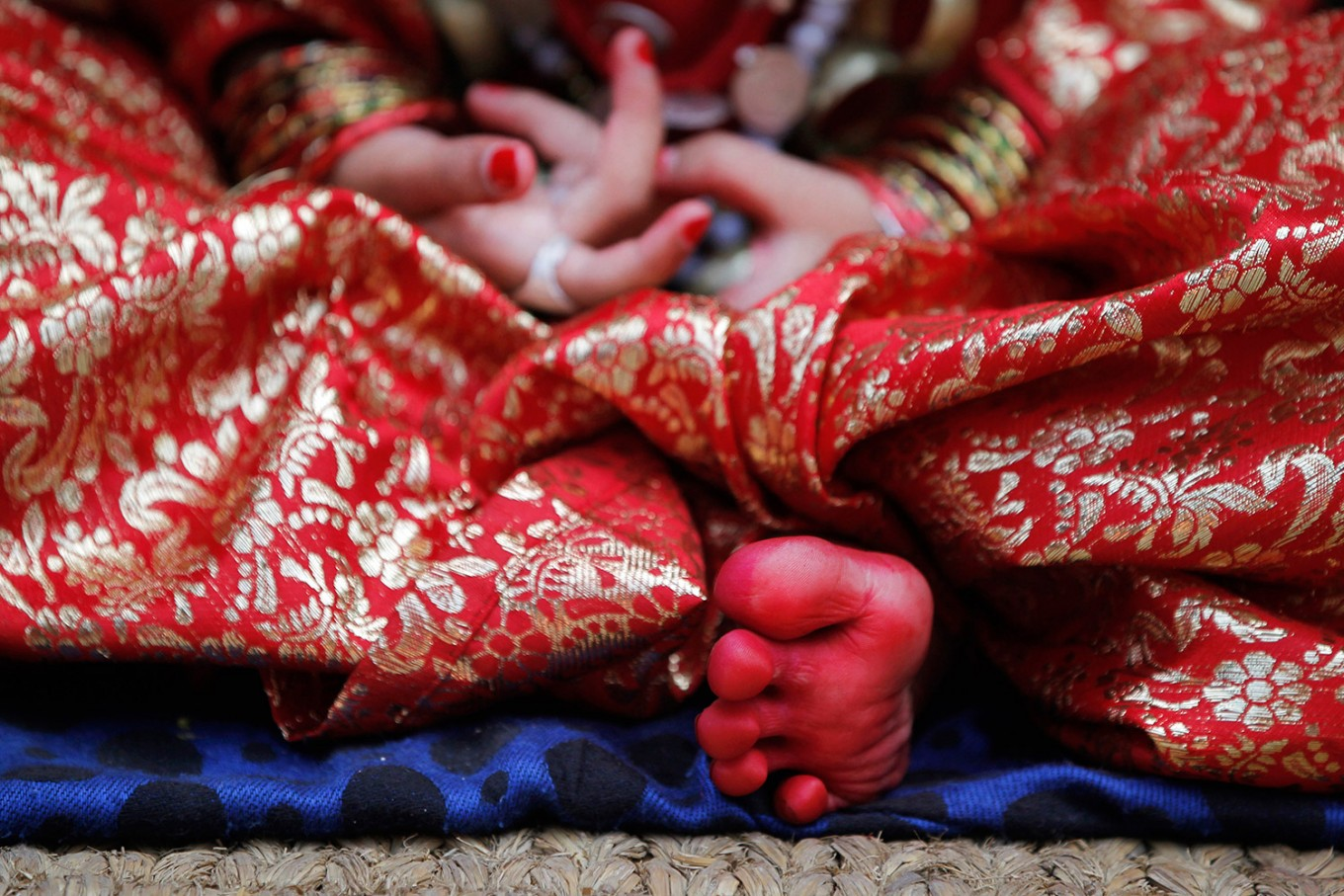 A Nepalese girl, wearing traditional attire with her feet dipped in vermillion paste, waits for Kumari puja to start at the Hanuman Dhoka temple, in Kathmandu, Nepal, Wednesday, Sept. 14, 2016.  AP Photo/Niranjan Shrestha