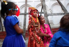A Nepalese woman gets photographed with a young girl dressed as the Living Goddess Kumari while waiting for the Kumari puja to start at Hanuman Dhoka temple, in Kathmandu, Nepal, Wednesday, Sept. 14, 2016. AP Photo/Niranjan Shrestha