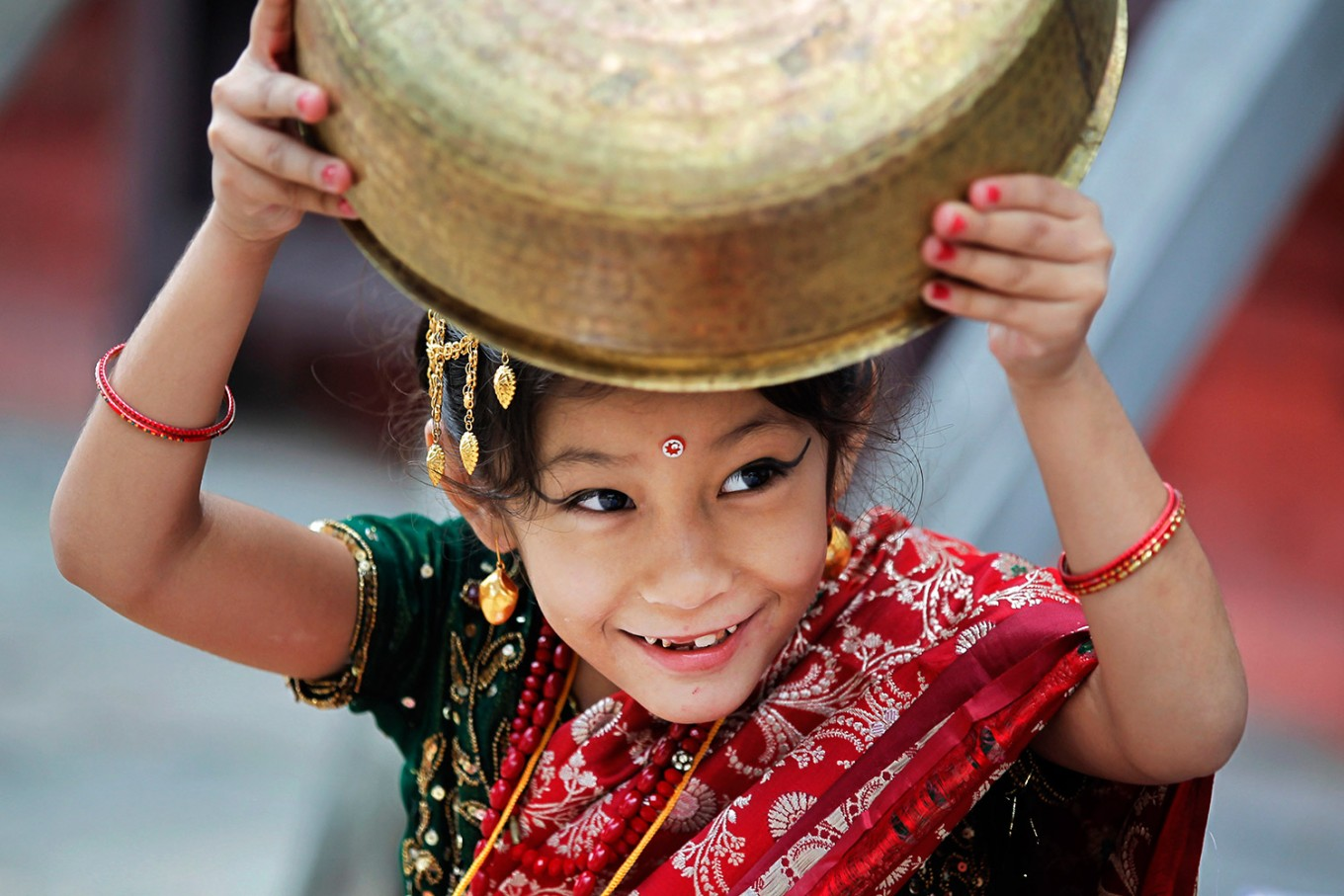 A young Nepalese girl wearing traditional attire plays with a vessel while waiting for the Kumari puja to start at Hanuman Dhoka temple, in Kathmandu, Nepal, Wednesday, Sept. 14, 2016.  AP Photo/Niranjan Shrestha