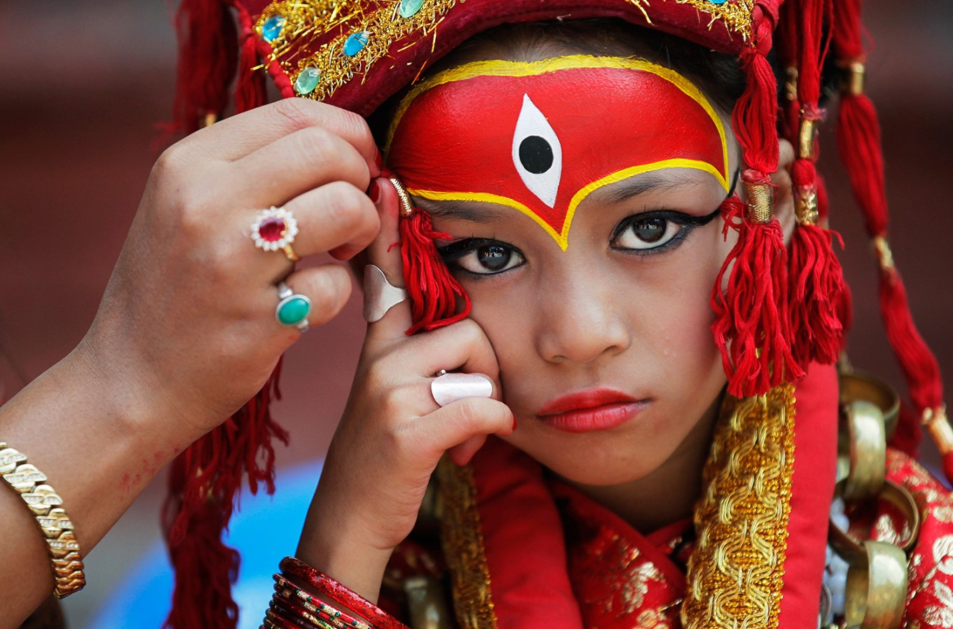 A Nepalese mother applies make up to her daughter dressed as the living goddess Kumari as they wait for Kumari puja to start at Hanuman Dhoka temple, in Kathmandu, Nepal, Wednesday, Sept. 14, 2016.