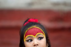A young Nepalese girl wearing traditional attire waits for the Kumari puja to start at Hanuman Dhoka temple, in Kathmandu, Nepal, Wednesday, Sept. 14, 2016. AP Photo/Niranjan Shrestha