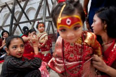 Young Nepalese girls wearing traditional costumes wait for the Kumari puja to start at Hanuman Dhoka temple, in Kathmandu, Nepal, Wednesday, Sept. 14, 2016. AP Photo/Niranjan Shrestha