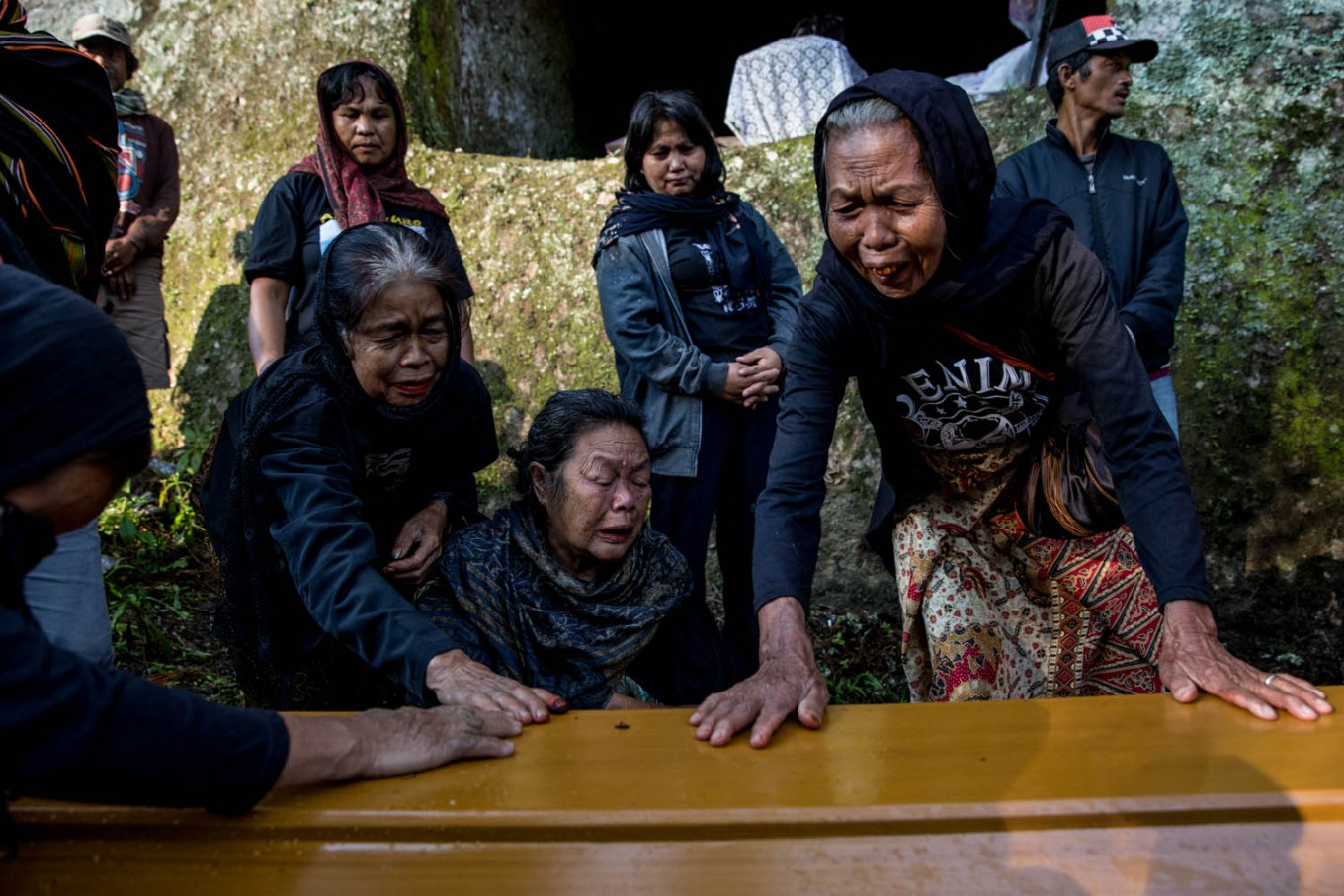 "Relatives cry as a coffin containing the corpses of Tikurara, Dumak and Limbongbuak arrive at a cliff-face grave called ""liang"" in Barrupu village, Toraja, South Sulawesi. JP/Agung Parameswara"