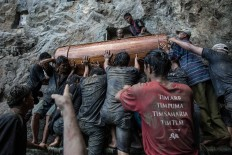 Men haul a coffin up a craggy cliff face in the Tana Toraja highlands JP/ Agung Parameswara