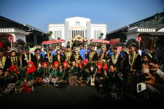 Couples pose together with makeup artists and wedding committee members after they exchanged vows at a mass wedding in the yard of Tugu Station in Yogyakarta on Sept. 6. JP/ Aditya Sagita