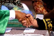 A groom shakes the hand of a penghulu [Islamic wedding vow administrator] at a mass wedding in Tugu Station of Yogyakarta on the morning of Sept. 6.JP/ Aditya Sagita
