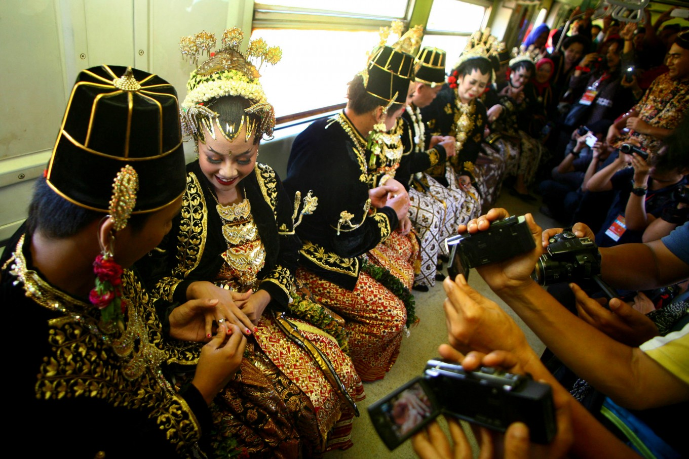 Couples put rings on their respective spouses onboard the Prambanan Express after exchanging vows at a mass wedding event in Yogyakarta on Sept. 6. JP/ Aditya Sagita