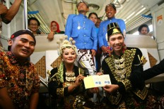 Newlywed couple Crysna Marsono and Kania Restu Fauzi show off their wedding book after exchanging vows aboard the running Prambanan Express, departing from Tugu Station in Yogyakarta to Solo Balapan station in Surakarta. JP/ Aditya Sagita