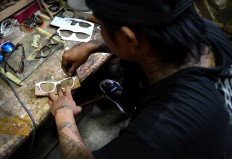 A craftsman draws a pattern for a frame on a piece of wood in a home workshop in Bandungrejo, Malang, in East Java. The frames are made by former drug addicts using wood recycled from used furniture. JP/Aman Rochman