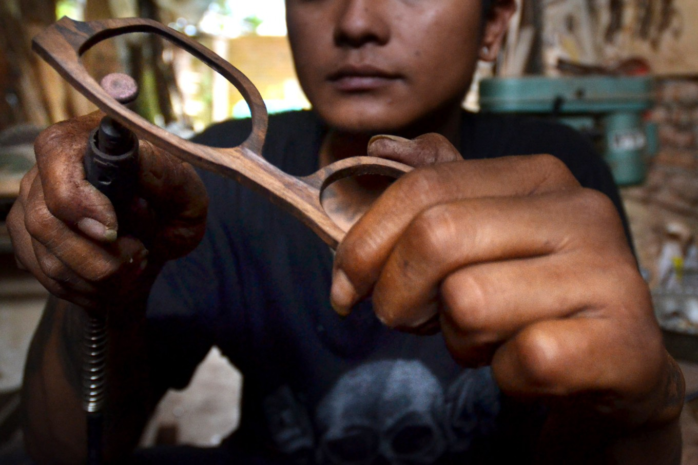 A worker makes a lens hood on a timber frame at a home workshop in Bandungrejo, Malang, East Java, on Aug. 15. JP/Aman Rochman