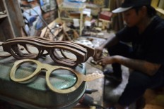 Fendi, 28, works on a wooden frame in a home workshop in Malang, East Java, on Aug. 15. The frames, made from recycled Indian rosewood and teak, are sold for between Rp 400,000 (US$30) and Rp 500,000. JP/Aman Rochman