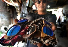 Mario Bannet, 32, shows several eye wear frames made by his friends at his workshop in Malang, East Java, on Aug. 15. JP/Aman Rochman