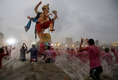 Devotees prepare to immerse an idol of elephant-headed Hindu god Ganesha in the Arabian Sea after worship marking the end of the 10-day long Ganesh Chaturti festival in Mumbai, India, Thursday, Sept. 15, 2016. The act symbolizes sending the god back to his mythical home in the snow-capped mountains taking all the worries and problems of his worshippers with him. AP Photo/Rajanish Kakade