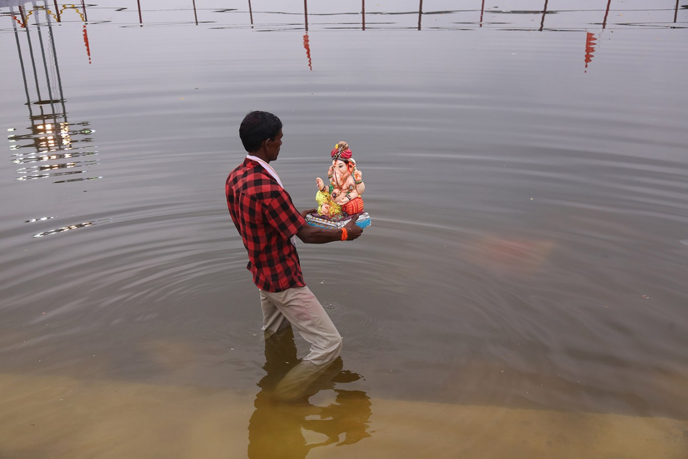 An Indian worker prepares to immerse an idol of elephant-headed Hindu god Ganesha in a lake during Ganesh Chaturthi festival in Hyderabad, India, Tuesday, Sept. 13, 2016. The immersion of idols after worship marks the end of the annual festival. AP Photo/Mahesh Kumar A.