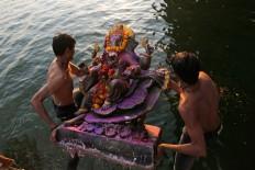 An Indian man holds idols of elephant-headed Hindu God Ganesha and jumps into the river Sabarmati to immerse them during Ganesha Chaturthi festival in Ahmadabad, India, Wednesday, Sept. 14, 2016. The ten-day festival is dedicated to the worship of Ganesha. AP Photo/Ajit Solanki