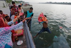 Indian men hold an idol of elephant-headed Hindu God Ganesha and jump into the river Sabarmati to immerse it during Ganesha Chaturthi festival in Ahmadabad, India, Wednesday, Sept. 14, 2016. The ten-day festival is dedicated to the worship of Ganesha. AP Photo/Ajit Solanki