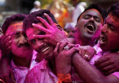 A Hindu devotee smears the face of another with colored powder during a procession for the immersion of idols of elephant-headed Hindu god Ganesha in the River Tawi on the last day of the ten-day long Ganesh Chaturthi Festival in Jammu, India, Thursday, Sept. 15, 2016. The last day of the 10-day celebration is the biggest day, with massive crowds singing and dancing as they carry their idols through the streets, to immerse them in the water, an act that symbolizes sending the god back to his mythical home in the snow-capped mountains taking all the worries and problems of his worshippers with him. AP Photo/Channi Anand