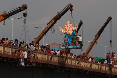Indian devotees watch as a crane lifts an idol of elephant-headed Hindu god Ganesha to immerse it in river Sabarmati on the final day of the ten-day long Ganesh Chaturthi festival in Ahmadabad, India, Thursday, Sept. 15, 2016. AP Photo/Ajit Solanki