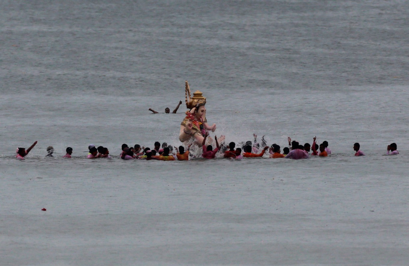Devotees splash water as they prepare to immerse an idol of elephant-headed Hindu god Ganesha in the Arabian Sea after worship marking the end of the 10-day long Ganesh Chaturti festival in Mumbai, India, Thursday, Sept. 15, 2016. The act symbolizes sending the god back to his mythical home in the snow-capped mountains taking all the worries and problems of his worshippers with him. AP Photo/Rafiq Maqbool