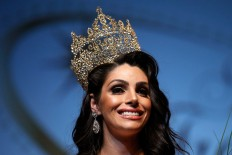 In this Sunday, Sept. 18, 2016 photo, the representative of Brazil, Rafaela Manfrini, smiles wearing the crown of the new Miss International Trans Star 2016, during a show celebrated in Barcelona, Spain. To be eligible to compete, contestants are not required to have undergone gender reassignment surgery, but must have the face and figure that comports with traditional notions of what constitutes ideal feminine beauty.