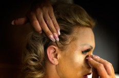 In this Sunday, Sept. 18, 2016 photo, Britanie Eichenholc, from France, applies make up ahead of the Miss Trans Star International 2016 show celebrated in Barcelona, Spain.