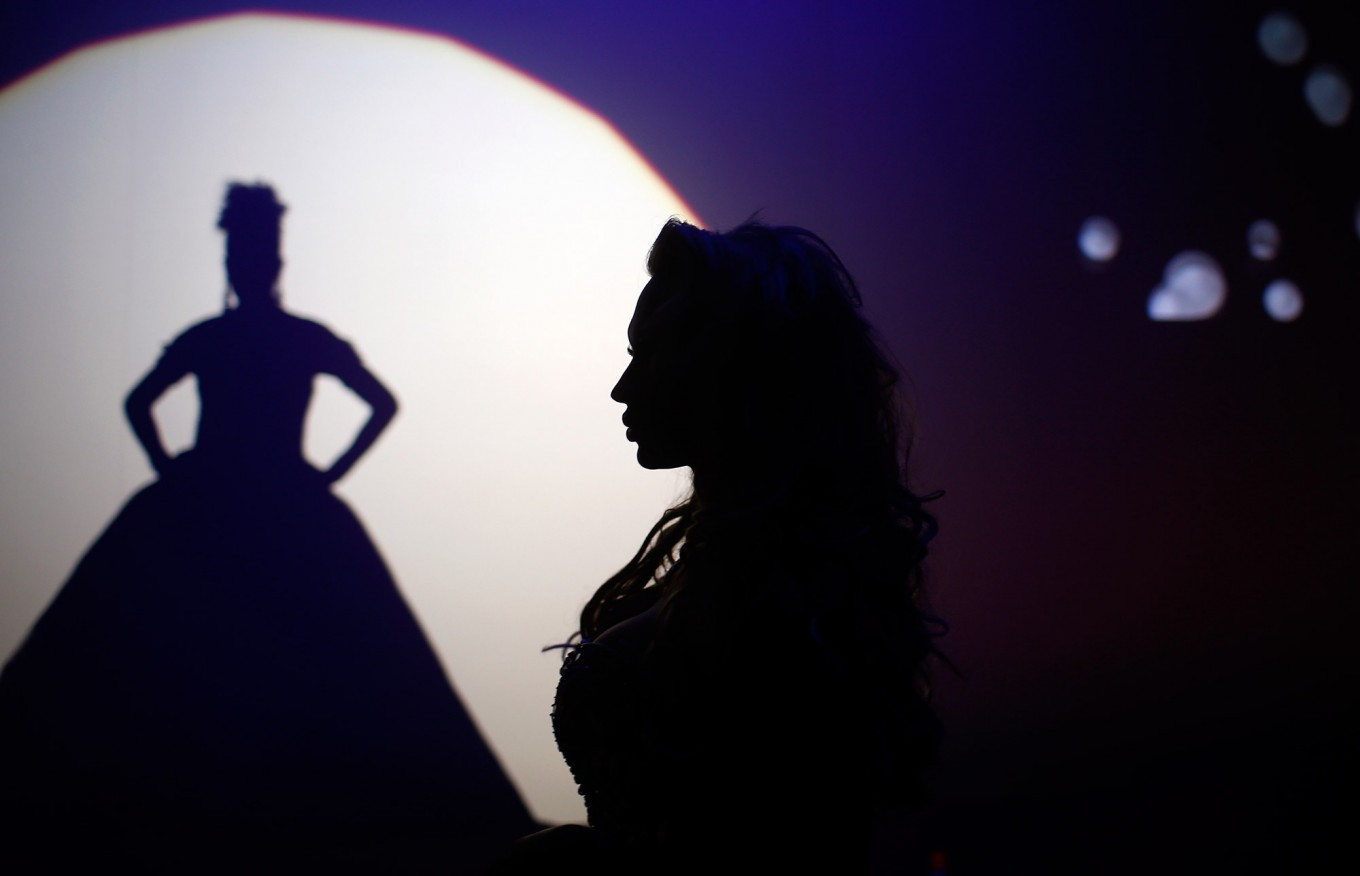 In this Sunday, Sept. 18, 2016 photo, Britanie Eichenholc, from France, right, is seen silhouetted during her performance at the Miss Trans Star International 2016 show celebrated in Barcelona, Spain.