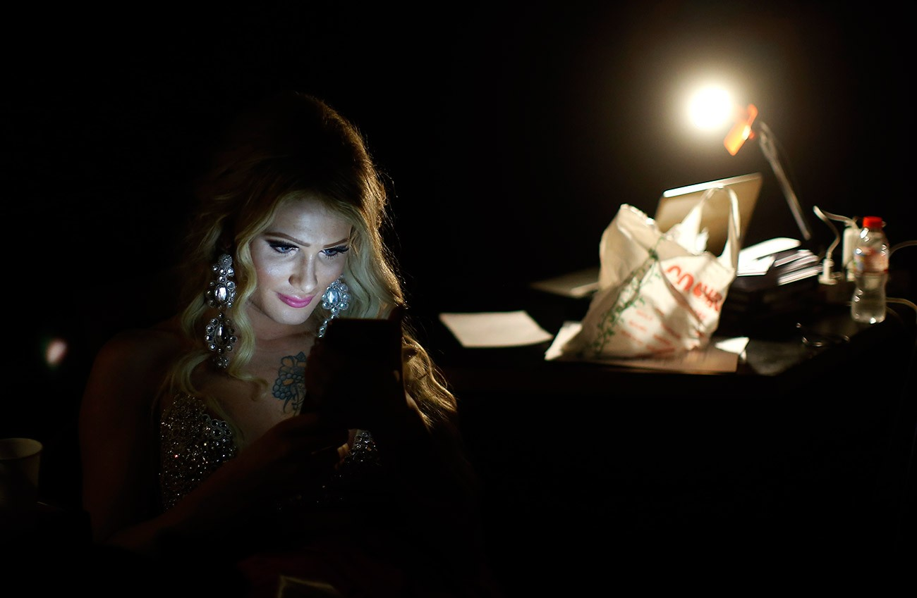 In this Sunday, Sept. 18, 2016 photo, Paris Nemc from Slovakia, looks at her phone during an interval at Miss Trans Star International 2016 show celebrated in Barcelona, Spain. Twenty-eight women representing as many countries competed last weekend to be crowned  Miss Trans Star International, Europe's largest beauty pageant for transgender women and one of a growing number of similar events aimed at celebrating a population more often condemned.