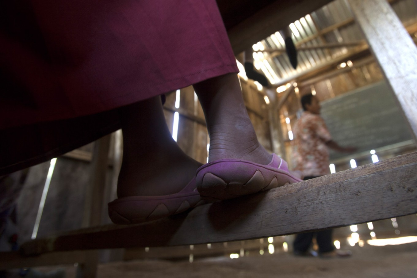 A student with her sandals observes teacher during the class. There are seven from 36 students who wear shoes to school. JP/ Sigit Pamungkas