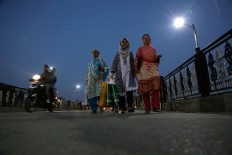 Kashmiri women walk back to their homes after shopping  during a relaxation from strike and curfew in Srinagar, Indian controlled Kashmir, Sunday, Sept. 25, 2016. Kashmir is witnessing the largest protests against Indian rule in recent years, sparked by the July 8 killing of a popular rebel commander by Indian soldiers.  AP Photo/Mukhtar Khan