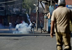 A Kashmiri Muslim protester throws an exploded tear smoke shell on Indian police during a protest in Srinagar, Indian controlled Kashmir, Sunday, Sept. 25, 2016. Kashmir is witnessing the largest protests against Indian rule in recent years, sparked by the July 8 killing of a popular rebel commander by Indian soldiers. AP Photo/Mukhtar Khan