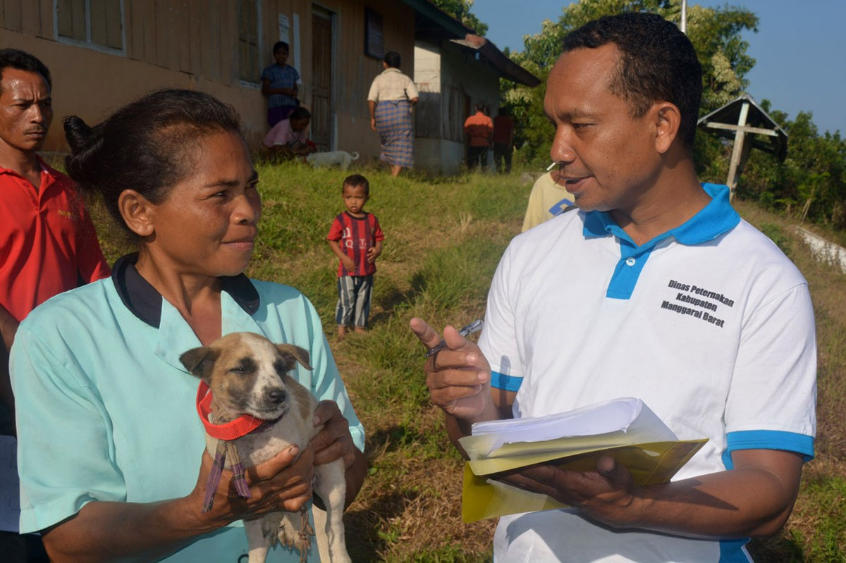 A health officer records data on vaccinated dogs belonging to residents in Kampung Melo on Aug. 31. JP/ Markus Makur