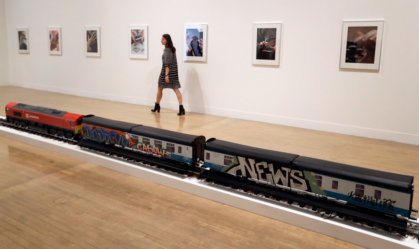 A woman walks past part of an artwork by Josephine Pryde, one of the four artists shortlisted for the Turner Prize 2016, as it is displayed at the Tate Britain gallery in London, Monday, Sept. 26, 2016. The Turner Prize aims to promote public debate around new developments in contemporary British art. AP Photo/Kirsty Wigglesworth