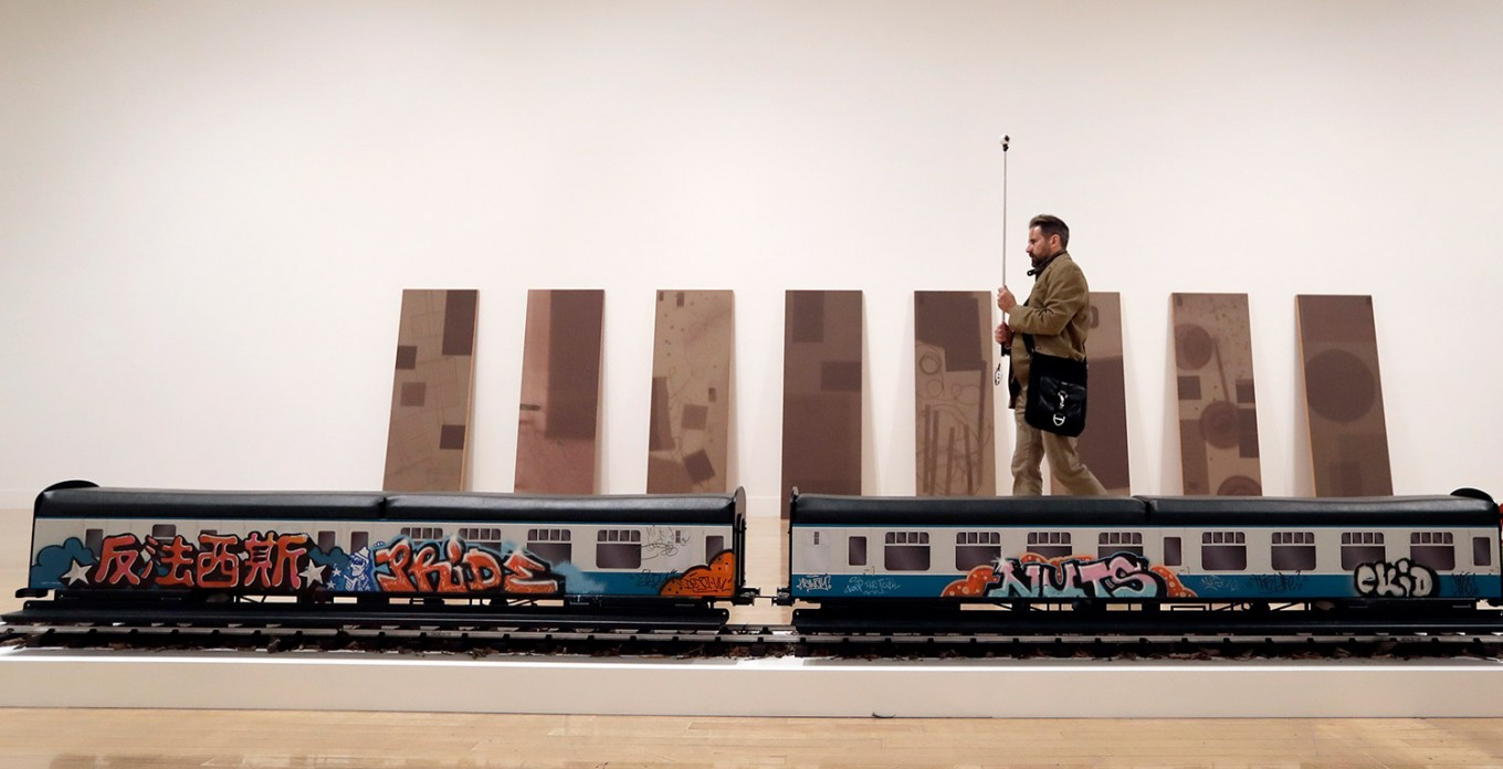 A man films part of an artwork by Josephine Pryde, one of the four artists shortlisted for the Turner Prize 2016, as it is displayed at the Tate Britain gallery in London, Monday, Sept. 26, 2016. The Turner Prize aims to promote public debate around new developments in contemporary British art. AP Photo/Kirsty Wigglesworth