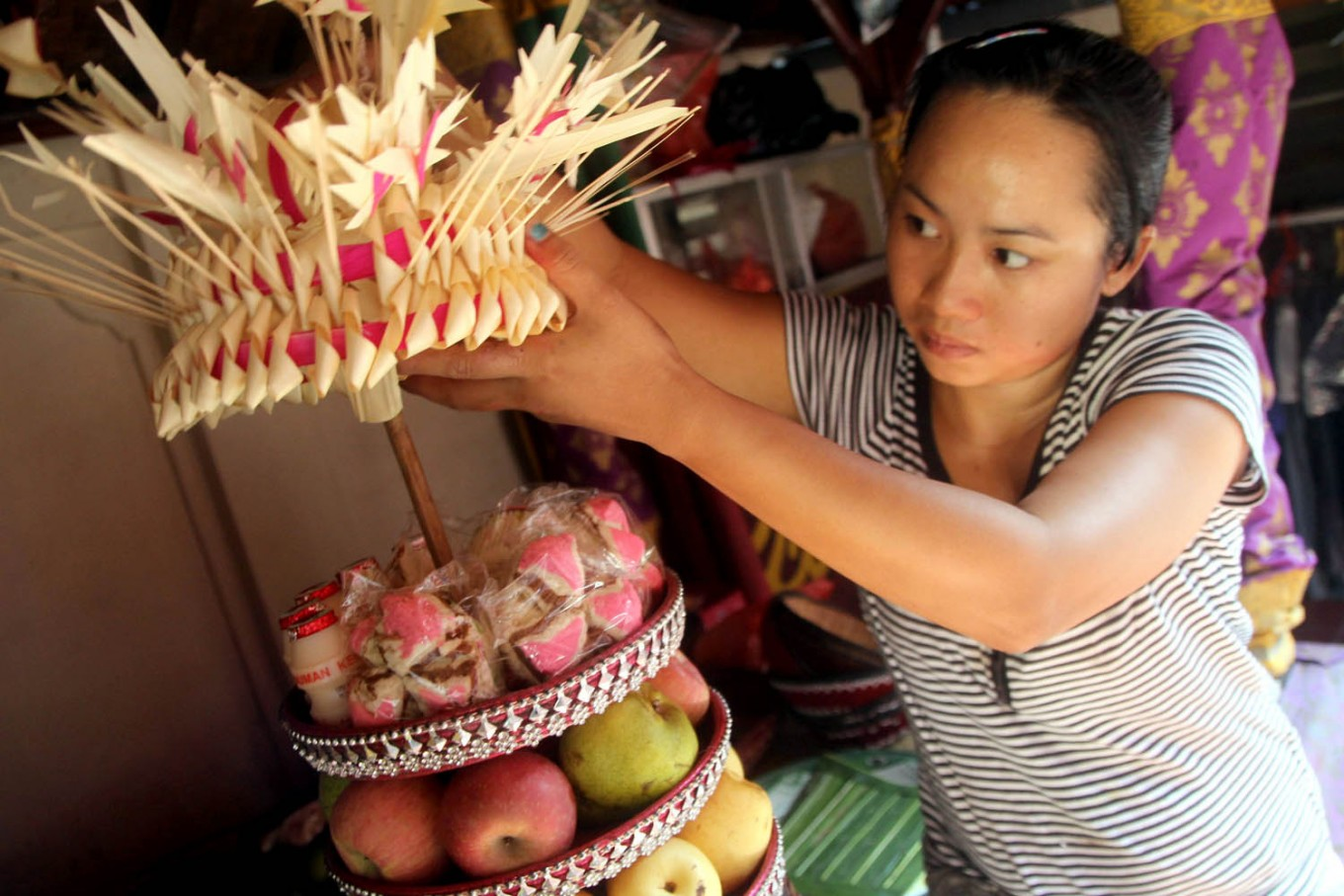 A woman prepares an offering containing fruit and snacks. The offering will be taken to the temple as part of the prayers' procession in celebrating Galungan. JP/Zul Trio Anggono