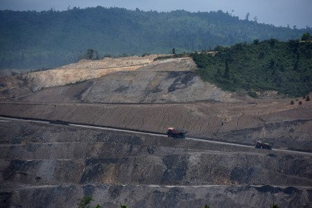 Heavy equipment and trucks pass through a coal mine in East Kalimantan.
