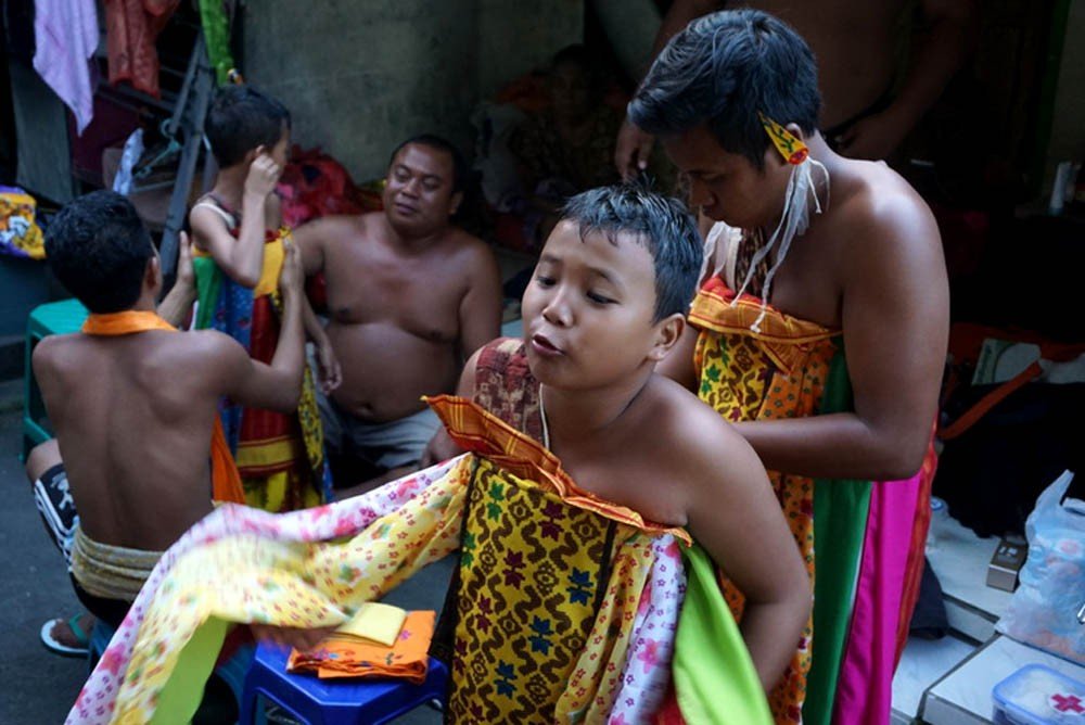 A boy gets help with his traditional attire.  It consists of woven cloth, colorful shawls, sacres yellow fabric and a kris. JP/ Luh De Suriyani